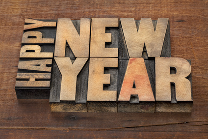 Happy New Year greetings or wishes - text in vintage letterpress wood type blocks on a grunge wooden background