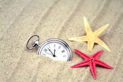 Pocket watch with starfish in the sand on the beach